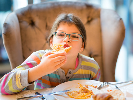 ni�os comiendo: Happy girl in glasses eating breakfast - egg omelet, toast, watermelon and tea - sitting in comfortable armchair