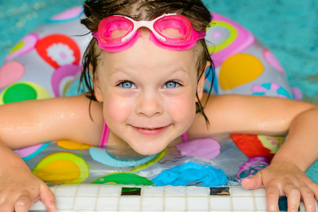 preserver: Funny little girl swimming in a pool in colorful life preserver