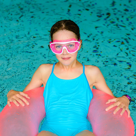 Happy young girl relaxing in pink life preserver in a swimming pool wearing pink goggles mask