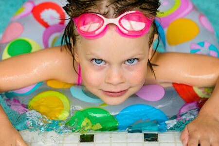little people: Funny little girl swimming in a pool in colorful life preserver