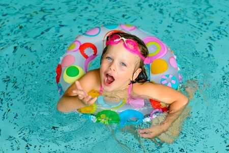 life preserver: Funny little girl swimming in a pool in colorful life preserver