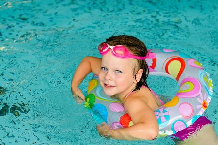 cute girl: Funny little girl swimming in a pool in colorful life preserver