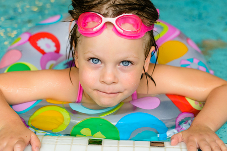 healthy girl: Funny little girl swimming in a pool in colorful life preserver