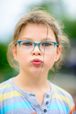 """Fille dans les lunettes avec les cheveux en désordre et le visage drôle connu comme «poisson-face"""""""