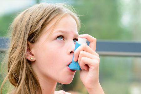 Muchacha que tiene asma usando el inhalador para el asma por ser saludable - profundidad de campo - concepto de alergia asma Foto de archivo