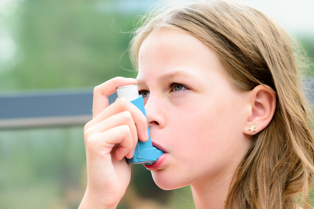 Girl having asthma using asthma inhaler for being healthy - shallow depth of field