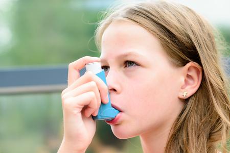 asthma: Muchacha que tiene asma con inhaladores de asma por ser saludable - profundidad de campo