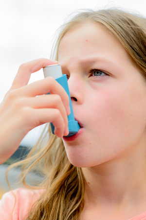 asthma: Girl having asthma using the asthma inhaler for being healthy - shallow depth of field - asthma allergy concept Stock Photo