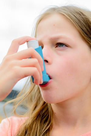 asthma: Muchacha que tiene asma usando el inhalador para el asma por ser saludable - profundidad de campo - concepto de alergia asma