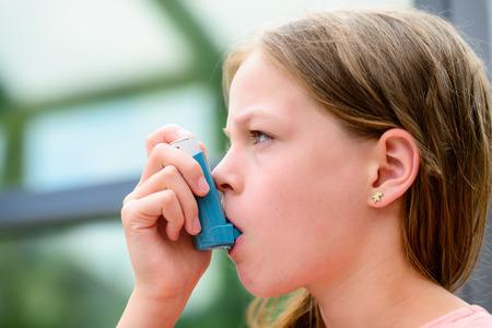 Girl uses an inhaler during an asthma attack, close-up Banco de Imagens