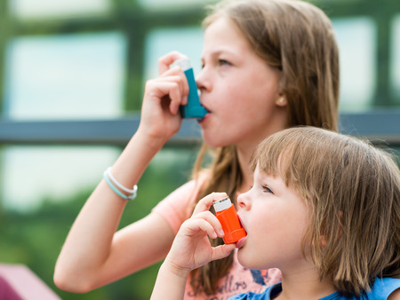 Girls having asthma using asthma inhaler for being healthy - shallow depth of field