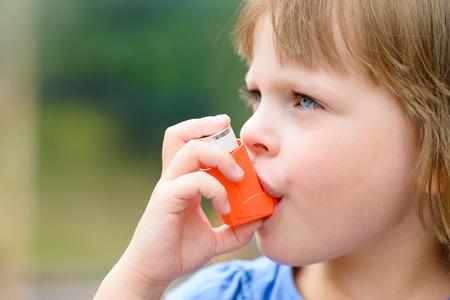 asma: Retrato de una chica que usa el inhalador del asma al aire libre Foto de archivo