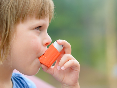 Portrait of a girl using asthma inhaler outdoors