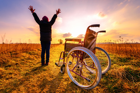 Miracle recovery: young girl gets up from wheelchair and raises hands up. Overjoyed young girl  standing up from a wheelchair outdoors. Shot in meadow. Recovery concept Archivio Fotografico