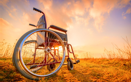 healed: Empty wheelchair on the meadow at sunset. Miracle concept. Healed person raised and went away Stock Photo