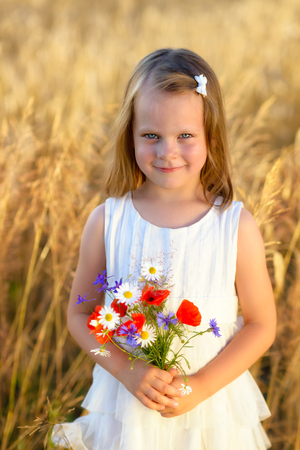 Cute little girl with wild flowers red poppy bouqet in the summer meadow