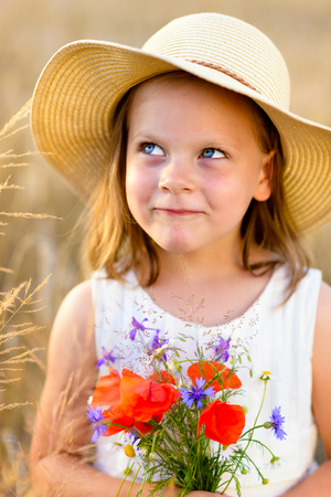 mischievous: Little cheerful girl in a straw hat with wild flowers red poppy bouquet in the summer meadow - coquettish, mischievous face