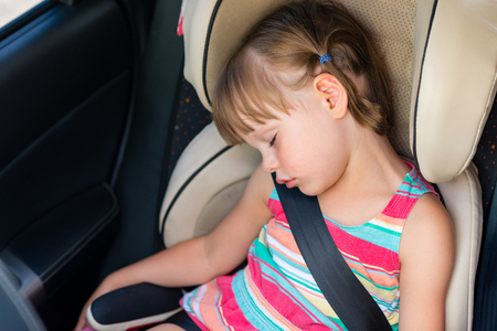 Toddler girl asleep in a child safety seat in a car