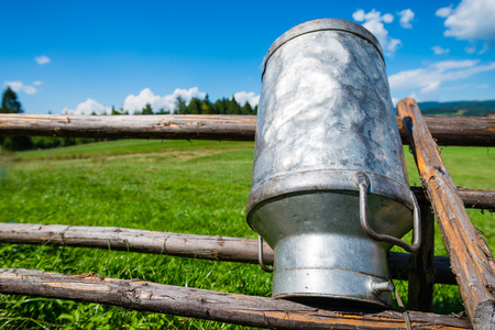 Old Milk Can Made of Aluminum. Old milk can made of metal to dry on a wooden stand - upside down - shallow depth of field Stock Photo