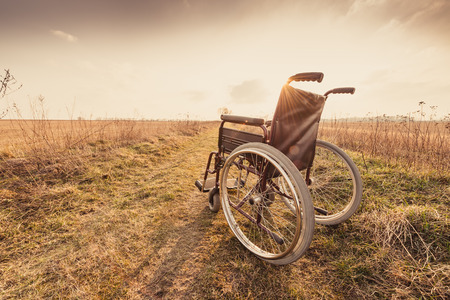 Empty wheelchair on the meadow at sunset. Miracle concept. Healed person raised and went away - retro vintage version
