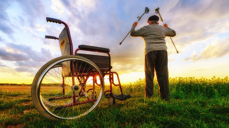 raises: Miracle recovery: Old man gets up from wheelchair and raises hands up. Shot in a meadow. Recovery concept Stock Photo