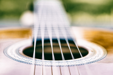 Acoustic guitar bridge and strings close up - macro - very shallow depth of field - vintage version