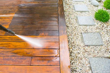 Reinigung Terrasse mit einem Hochdruckreiniger - Hochwasserdruckreiniger auf Holzterrassenfläche Standard-Bild