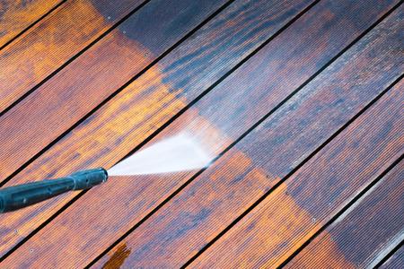 schoonmaken terras met een hogedrukreiniger - hoog water hogedrukreiniger op houten terras oppervlak