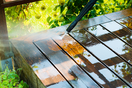 cleaning terrace with a power washer - high water pressure cleaner on wooden terrace surface Imagens - 69081315