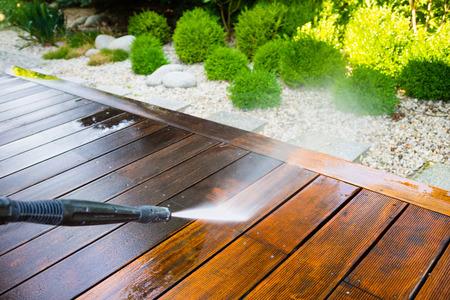 terraza de limpieza con una arandela de la energía - limpiador de alta presión de agua en la superficie de terraza de madera Foto de archivo