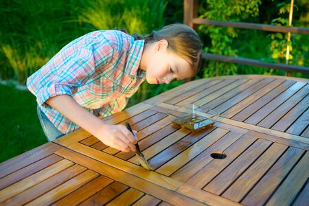 Young pretty girl holding a brush applying varnish paint on a wooden garden table