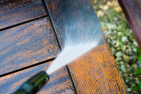 cleaning terrace with a power washer - high water pressure cleaner on wooden terrace surface Фото со стока - 69120426