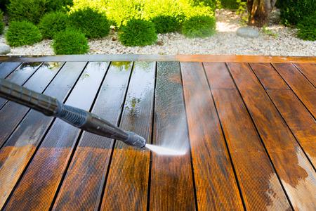 Terraza de limpieza con una arandela de la energía - limpiador de alta presión de agua en la superficie de terraza de madera Foto de archivo - 69050970
