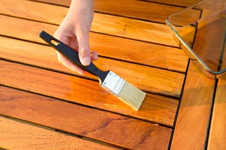 Hand mit einem Pinsel anwenden Lackfarbe auf einem hölzernen Gartentisch - Malerei und Holzpflegeöl-Wachs Standard-Bild