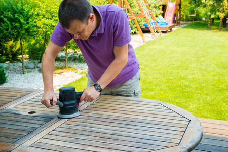 Young man - carpenter working with electric sander in the garden - polishing old color from wooden table Stock Photo