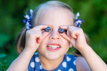 Smiling girl showing blueberries in front of her face - covering her eyes with blueberries Фото со стока
