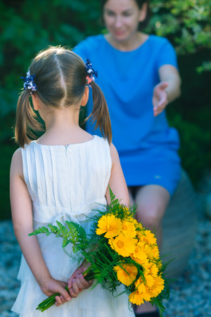 Happy mothers day! Child girl congratulates mom and gives her bouquet of yellow flowers - very shallow depth of field (focus on flowers)