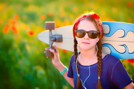 Young hipster girl with braids in sunglasses and a red sash on her head, listening to music with a longboard on her shoulders - against a summer meadow at sunset