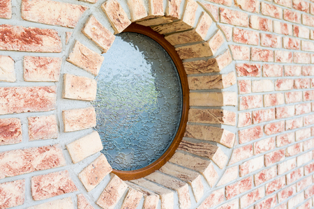 Round window on brick wall - shallow depth of field - focus on the closer arch of the window Stock Photo