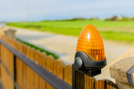 Automatic gate - wooden gate with warning lamp detail - close up