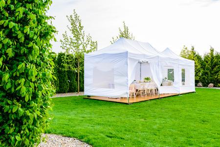 Party tent - white garden party or wedding entertainment tent in modern garden Standard-Bild