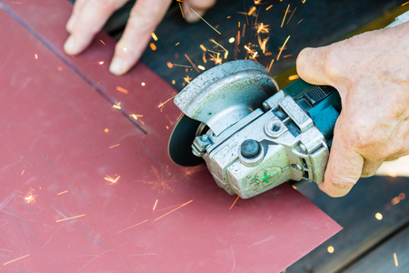sawing metal with electric grinder Фото со стока - 84513228