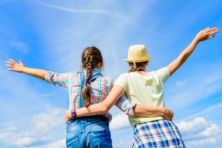 Happy friends with open arms under blue sky.  Two girls having fun - relax outdoors. Friendship happiness summer holidays concept