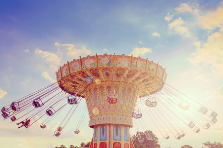Wave Swinger ride against blue sky, vintage filter effects - a swinging carousel fair ride at dusk 免版税图像 - 86187361