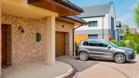 Woonhuis met zilveren suv-auto geparkeerd op oprijlaan vooraan. Familiehuis - perfect buurtconcept Stockfoto