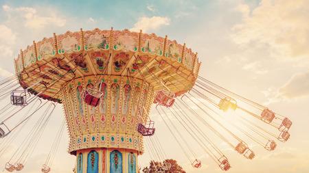 el paseo en carrusel gira rápido en el aire al atardecer - efectos de filtro vintage - un carrusel de feria justo al atardecer Foto de archivo