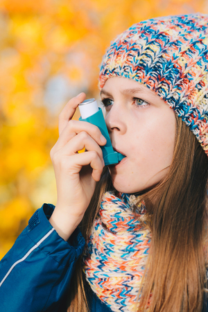 Young girl using asthma inhaler in a park - chronic disease control, allergy induced asthma remedy and allergy disease concept Stock Photo