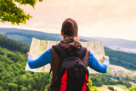 Hiking woman traveler with backpack checks map to find directions in wilderness area, real explorer. Travel Concept Stock Photo