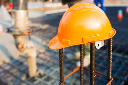 Orange safety helmet at construction site with blurry background Stock Photo