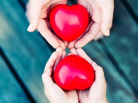 Hearts in hands on grey background Foto de archivo